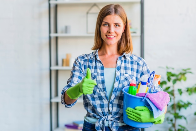 Het portret van een gelukkig dienstmeisje met emmer het schoonmaken van materiaal het gesturing beduimelt omhoog