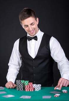Het portret van een gelukkige croupier houdt speelkaarten.