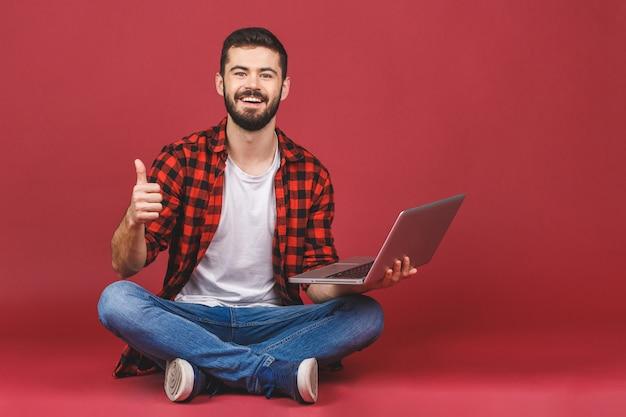 Het portret van een gelukkige jonge mens gebruikend laptop en tonend beduimelt omhoog gebaar