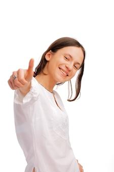 Het portret van een gelukkige jonge vrouw die duimen toont ondertekent omhoog over witte achtergrond