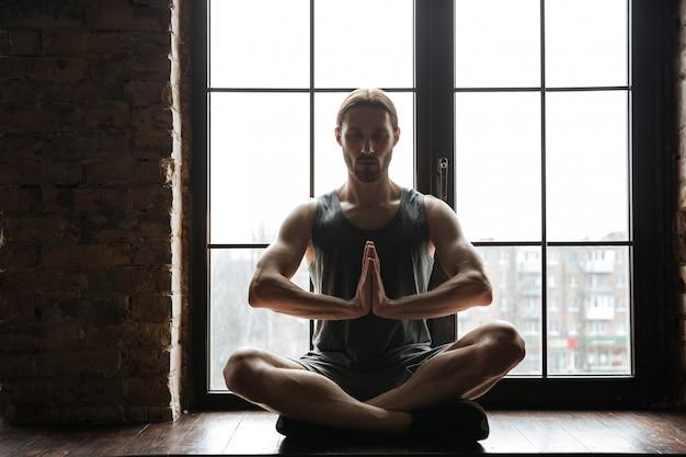 Het portret van een gezonde jonge sportman die in lotusbloem mediteren stelt