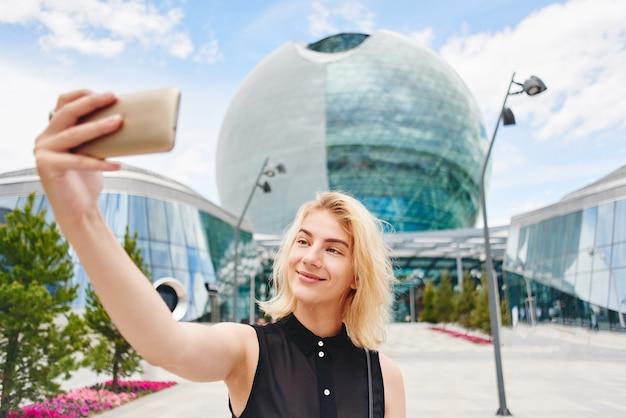 Het portret van een glimlachend blondemeisje in zwarte maakt selfie foto op cellphone op de achtergrond van een glas bedrijfsgebouw