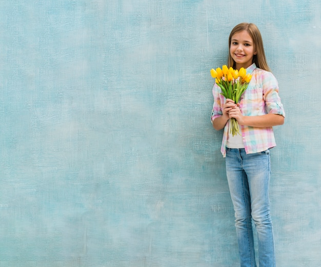 Het portret van een glimlachend meisje die gele tulp houden bloeit in hand status tegen blauwe muur
