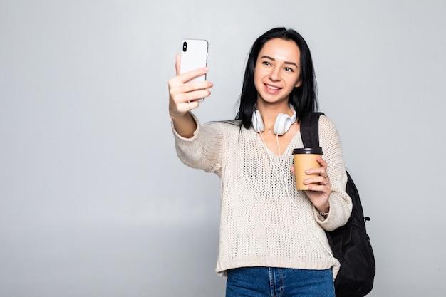 Het portret van een glimlachende aantrekkelijke vrouw die een selfie nemen terwijl het houden haalt koffiekop weg over witte muur wordt geïsoleerd die