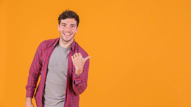 Het portret van een glimlachende jonge mens die duim toont ondertekent omhoog tegen een oranje achtergrond