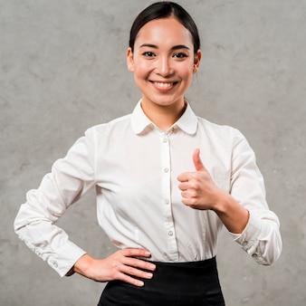 Het portret van een glimlachende jonge onderneemster met hand op haar heupen die duim tonen ondertekent omhoog
