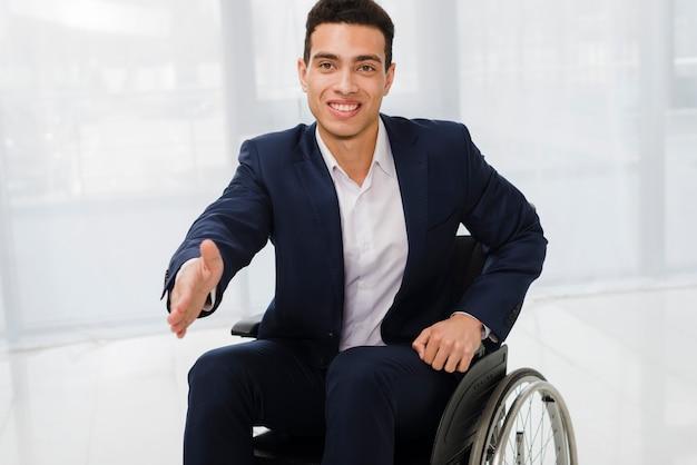 Het portret van een glimlachende jonge zakenman bereikt uit naar camera om handen te schudden