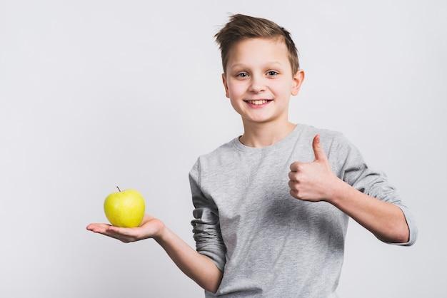 Het portret van een glimlachende jongen die groene appel op hand houdt die duim toont ondertekent omhoog