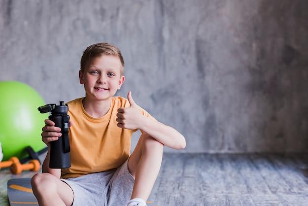 Het portret van een glimlachende jongenszitting met waterfles die duimen toont ondertekent omhoog