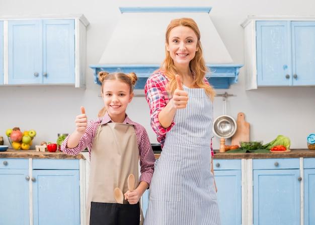 Het portret van een glimlachende moeder en haar dochter die duim tonen ondertekent omhoog in de keuken
