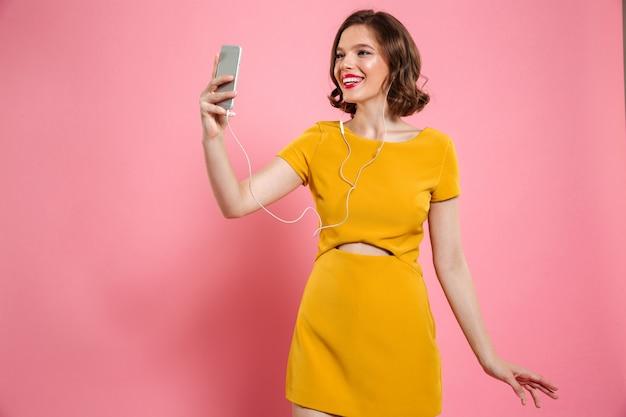 Het portret van een glimlachende vrouw in kleding en maakt omhoog