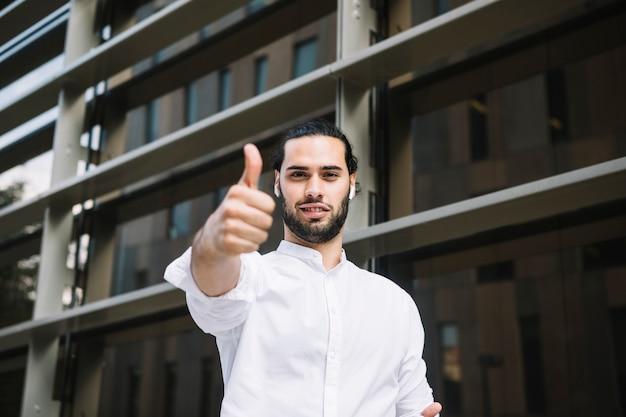 Het portret van een glimlachende zakenman die duim toont ondertekent omhoog