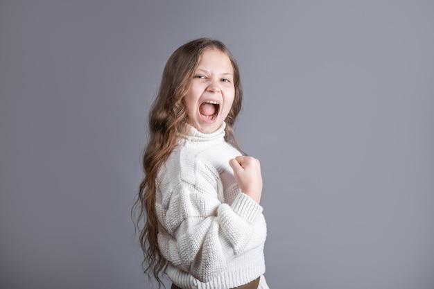 Het portret van een jong aantrekkelijk klein meisje met blond lang golvend haar in een witte sweater heft vuist op succesvol vieren op een grijze studioachtergrond. kopieer ruimte.
