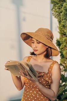 Het portret van een jong aziatisch meisje leest een boek in het park