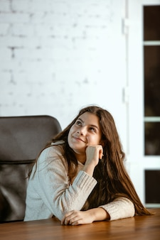 Het portret van een jong kaukasisch meisje in vrijetijdskleding ziet er dromerig, schattig en gelukkig uit