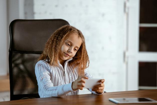 Het portret van een jong kaukasisch meisje ziet er dromerig, schattig en gelukkig uit. opzoeken, binnen zitten aan de houten tafel met tablet en smartphone. concept van toekomst, doel, droom om te kopen, visualisatie.
