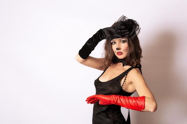 Het portret van een jong meisje in een zwarte jurk en zwarte en rode handschoenen met een hoed op haar hoofd