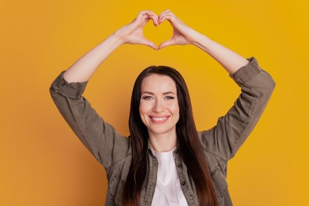 Het portret van een jong meisje toont het cijfer van het vingerhart over gele achtergrond