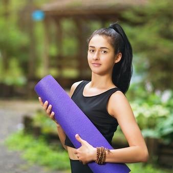Het portret van een jonge aantrekkelijke vrouw met een gymnastiekmat in haar dient het park in