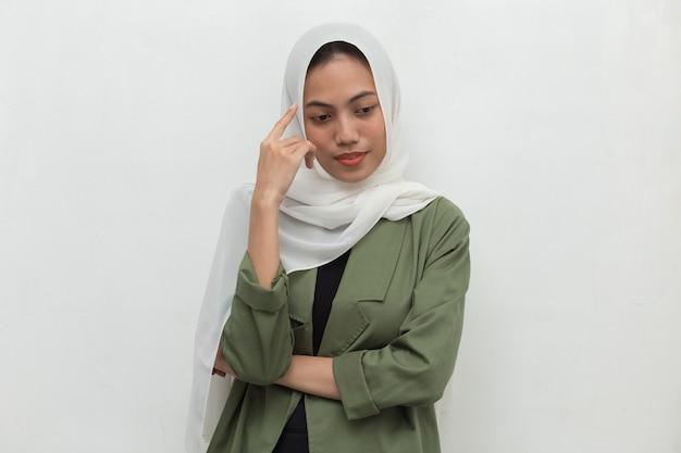 Het portret van een jonge aziatische moslimvrouw denkt