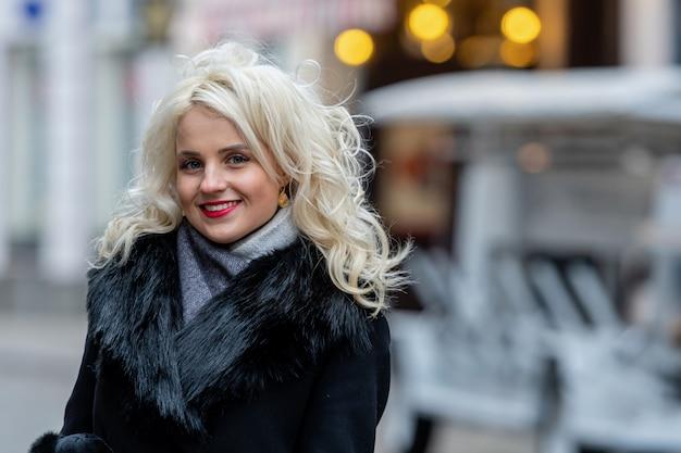 Het portret van een jonge glimlachende blondevrouw defocused straat. kopieer ruimte.