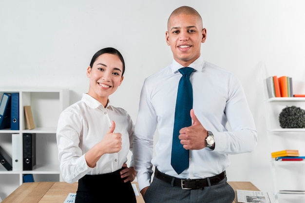 Het portret van een jonge glimlachende zakenman en een onderneemster die duim tonen ondertekenen omhoog