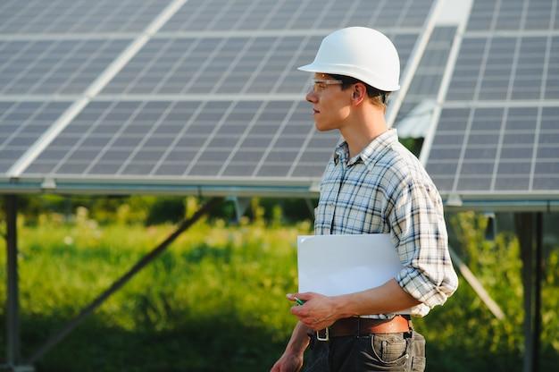 Het portret van een jonge ingenieur controleert fotovoltaïsche zonnepanelen