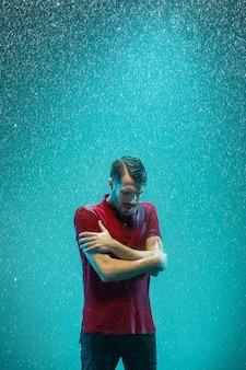 Het portret van een jonge man in de regen