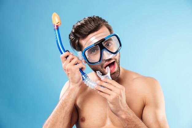 Het portret van een jonge mens die zwemmend masker draagt en snorkelt