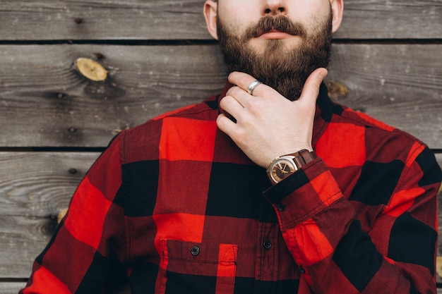 Het portret van een jonge modieuze gebaarde mens kleedde zich omhoog in jeans en een ware arbeiderszwarte door rood overhemd.