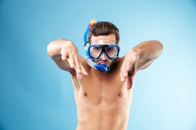 Het portret van een jonge shirtless kerel die snorkel en beschermende brillen draagt