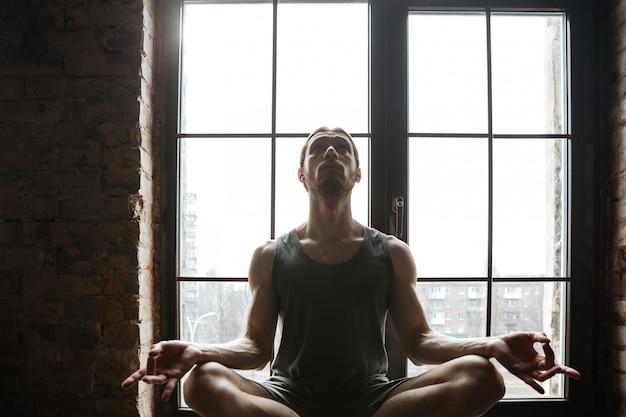Het portret van een jonge sportman die in lotusbloem mediteren stelt terwijl het zitten op de vensterbank bij de gymnastiek