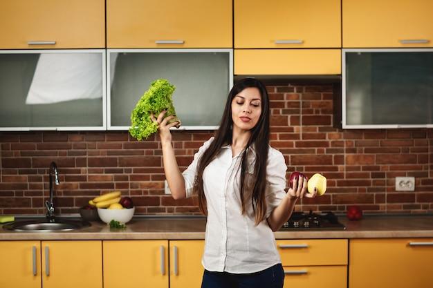 Het portret van een jonge vrouw houdt twee appelen en sla in haar handen. een vrouw die zich in de keuken thuis bevindt. het concept van voeding en gezond eten, het lichaam reinigen