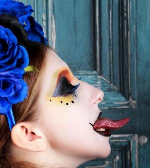 Het portret van een jonge vrouw met halloween maakt omhoog met blauwe bloemen