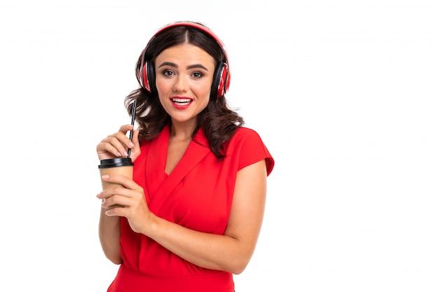 Het portret van een jonge vrouw met rode lippen luistert naar muziek in hoofdtelefoons, drinkt koffie en glimlacht