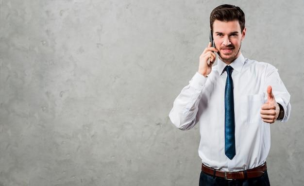 Het portret van een jonge zakenman die op mobiele telefoon spreken die duim tonen ondertekent omhoog tegen concrete grijze muur