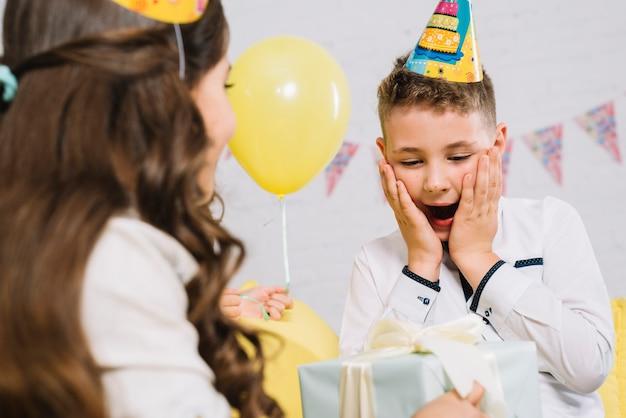 Het portret van een jongen wordt verrast na het ontvangen van giftdoos van haar vriend