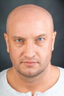 Het portret van een kale mens met blauwe ogen sluit omhoog