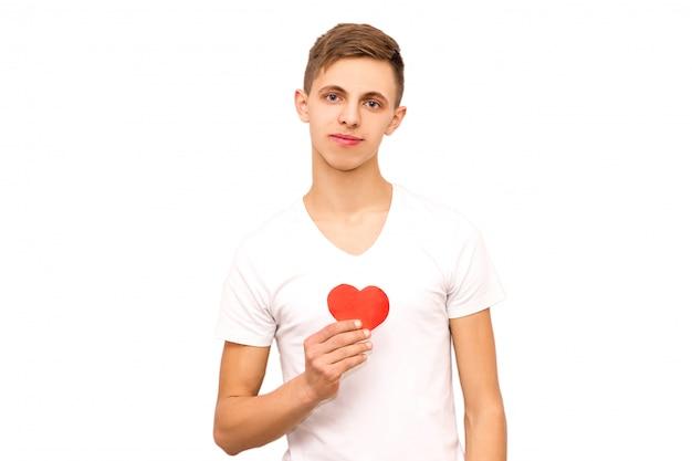 Het portret van een kerel in een witte t-shirt die een hart houdt, isoleert