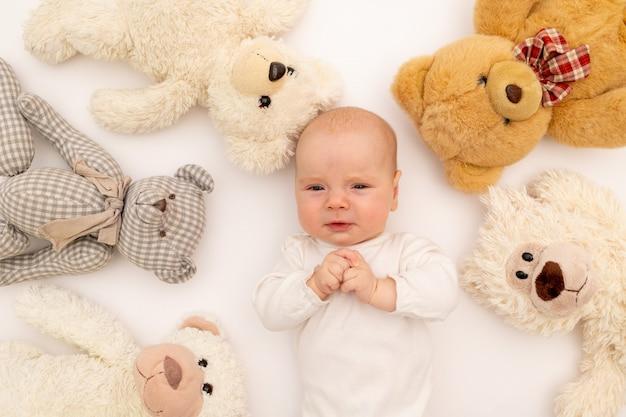 Het portret van een kind met pluche draagt speelgoed. baby 6 maanden onder speelgoed.