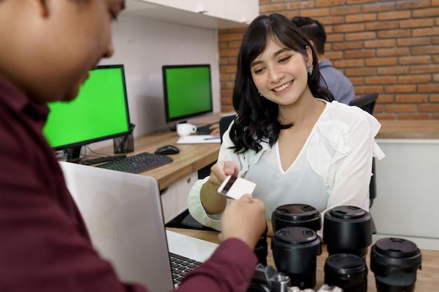 Het portret van een klant betaalt de rekening met creditcard in de camerahuurwinkel