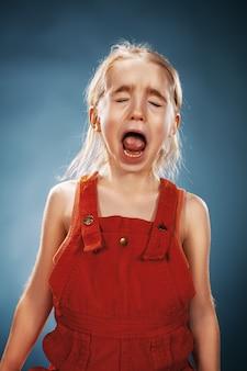 Het portret van een klein meisje in een rode jurk op een blauwe achtergrond. ze is aan het huilen