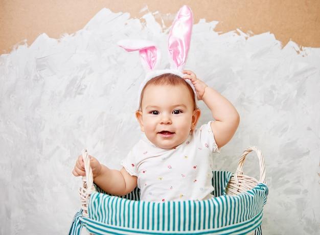 Het portret van een leuke baby gekleed in paashaasoren in een mand houdt ei