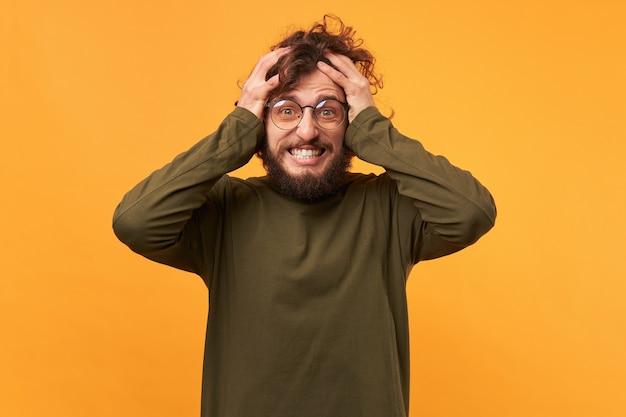 Het portret van een man met een bril met een baard tegen zijn hoofd geklemd ziet er blij verbaasd uit, overweldigd door emoties