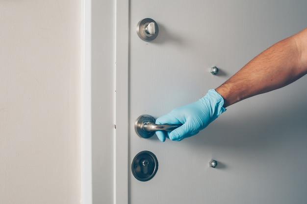 Het portret van een mens die bij ruimte de deur openen met dient handschoenen in