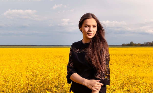 Het portret van een mooi jong meisje met lang haar in zwarte kleding bevindt zich op geel gebied.