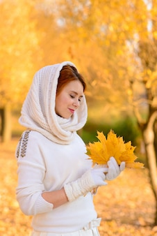 Het portret van een mooi jong roodharigemeisje met bloemen ziet er aantrekkelijk uit in een witte kleding