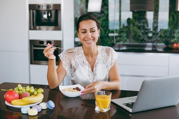 Het portret van een mooie gelukkige vrouw die met laptop werkt tijdens het ontbijt met ontbijtgranen en melk