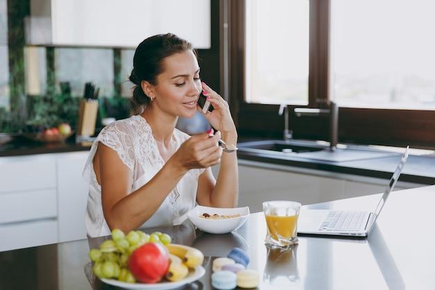 Het portret van een mooie gelukkige vrouw die op een mobiele telefoon praat tijdens het ontbijt met een laptop op tafel