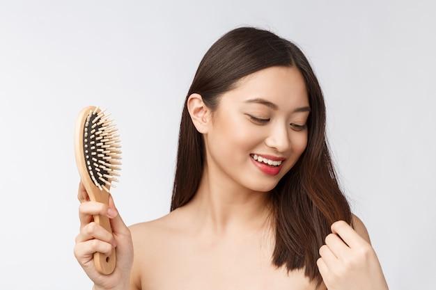 Het portret van een mooie jonge vrouw kamt prachtig die haar op witte achtergrond, aziatische schoonheid wordt geïsoleerd